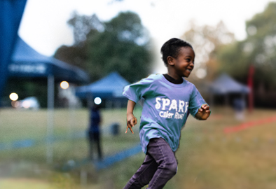 A kid smiles as they participate in an on-campus Fun Run.