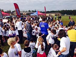 a large group of students parents and faculty at a boosterthon rally.
