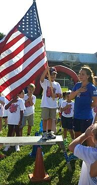 A student holds the flag for the national anthem.