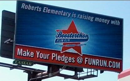 a roadside billboard advertises the Roberts elementary Boosterthon fun run.