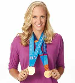 Dana Vollmer poses with her two Olympic gold medals for swimming.