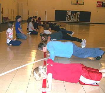 students participate in PE doing push-ups.