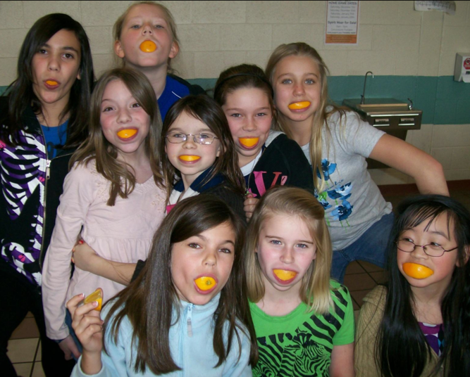 students take a group photo with orange slices in their mouth like mouth guards.