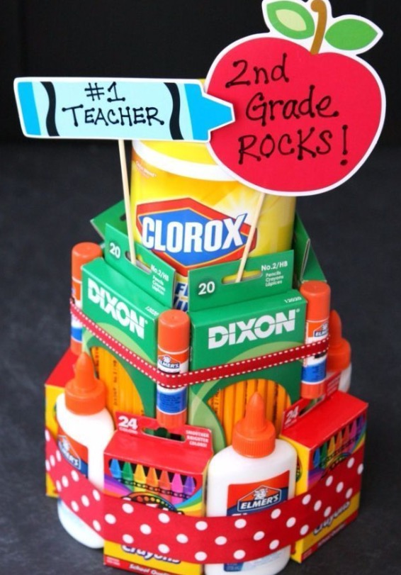 "A school supply ""cake"" composed of classroom supplies like glue, crayons, and pencils."