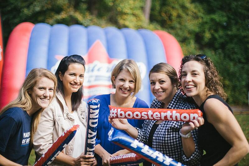 A group of mothers show off their Boosterthon school spirit cheering sticks.