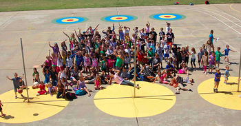 A group of students and Boosterthon team members pose for an aerial shot group photo.