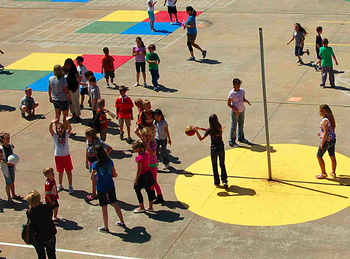 Aerial view of an elementary school playground with children playing at recess.