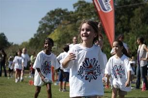 Kids playing at a fun run, sporting their Boosterthon t-shirts.