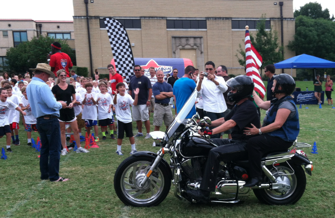 The school principal arriving via motorcycle to a Boosterthon event.