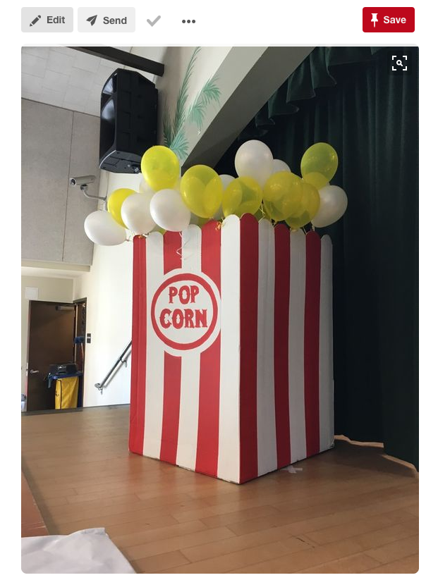 A decoration like a giant bag of red and white popcorn with white and yellow balloons.