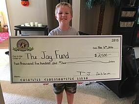Posing with a big check of raised funds.