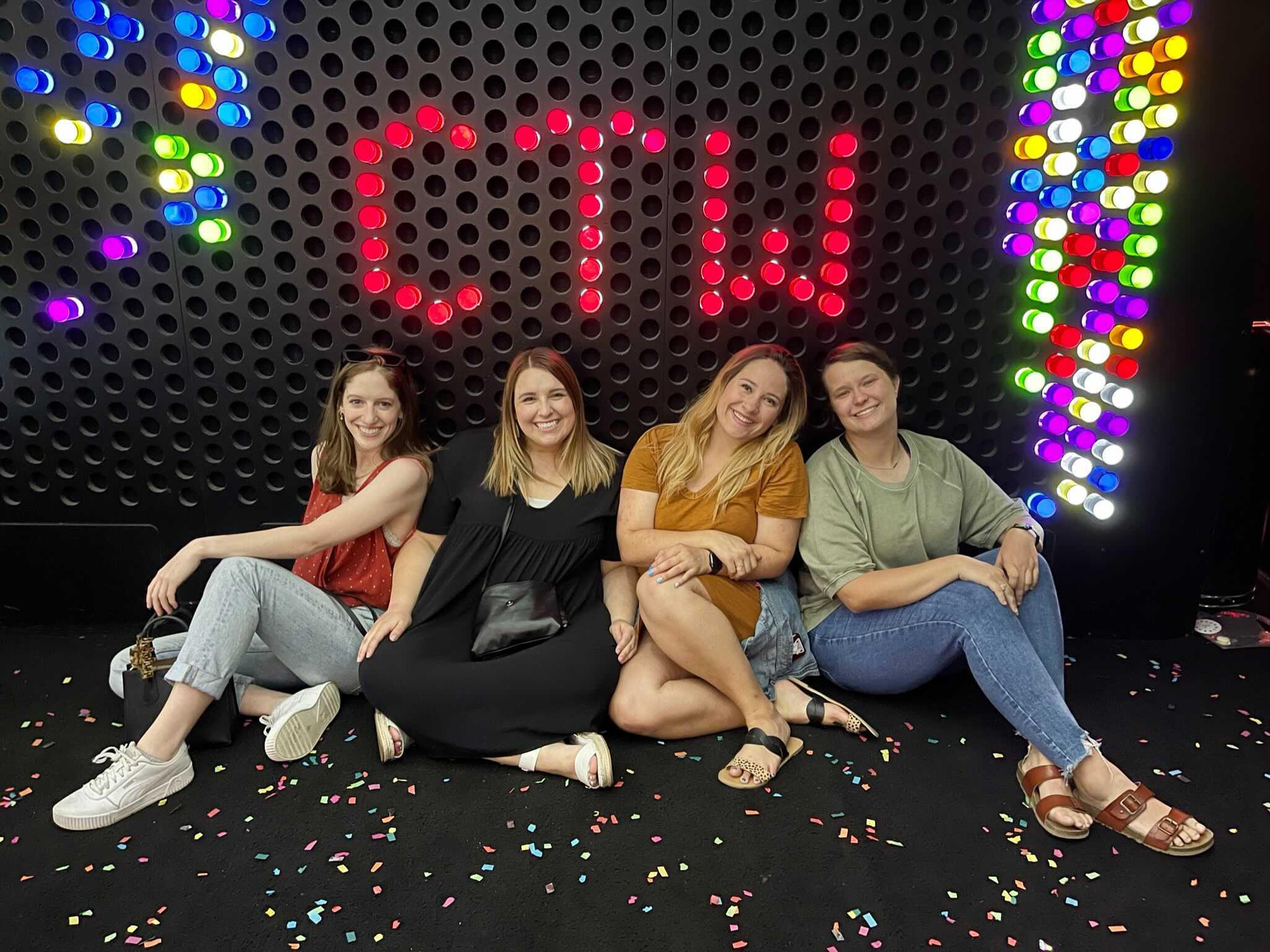 Women sitting in front of a CTW colored wall