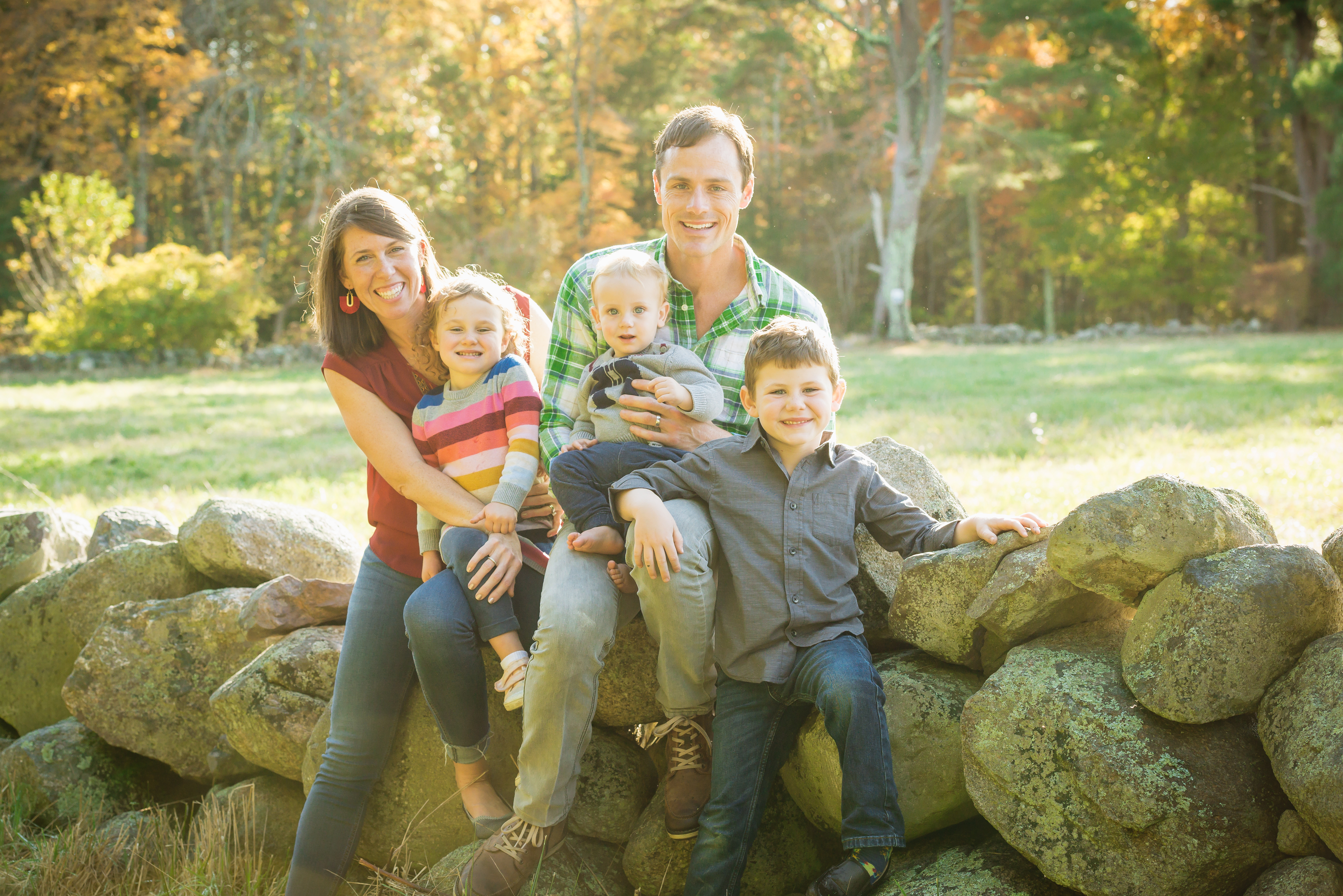 Image of family sitting on a rock ledge