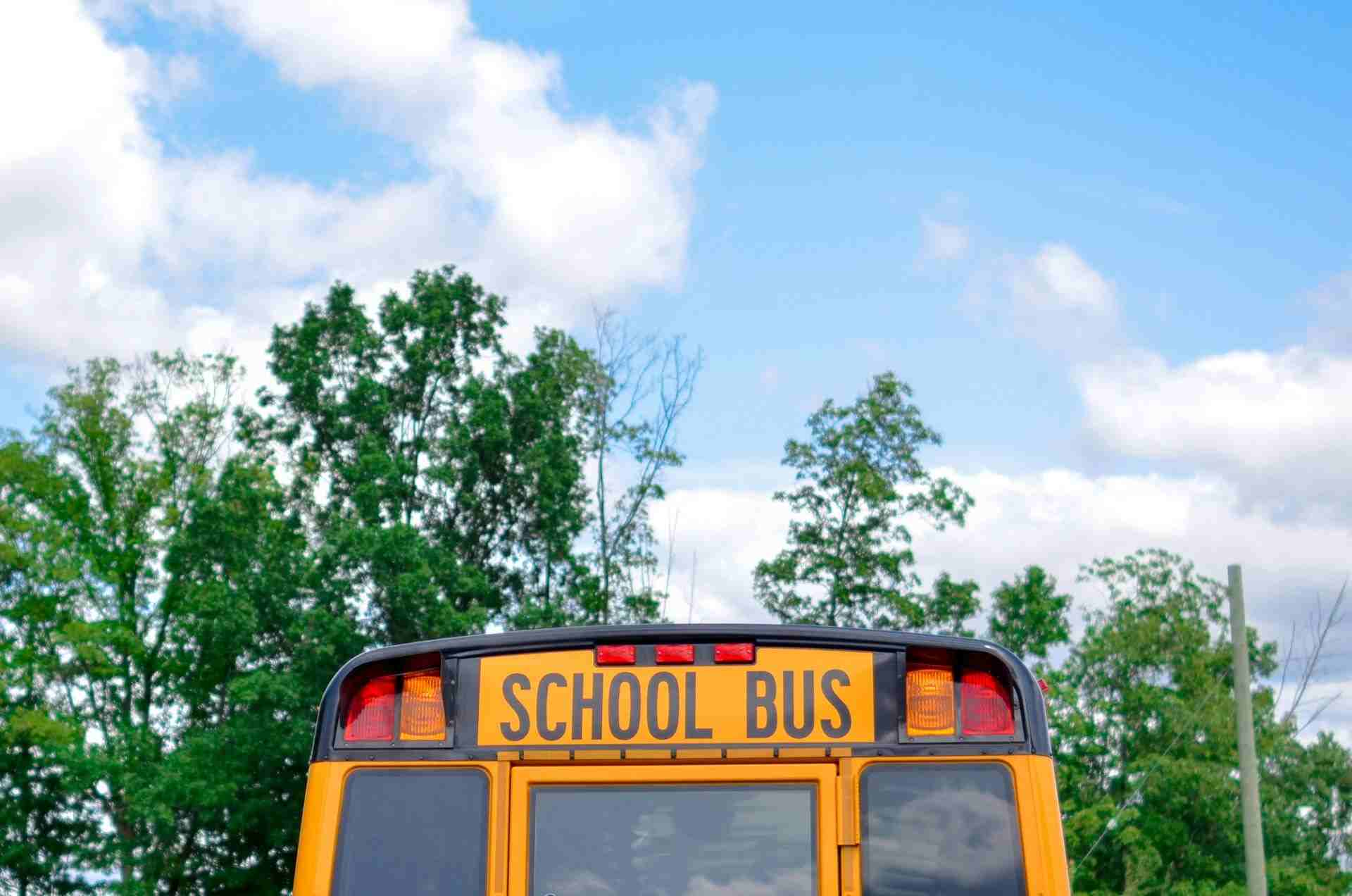 Back end of a yellow school bus, with a beautiful blue sky background.
