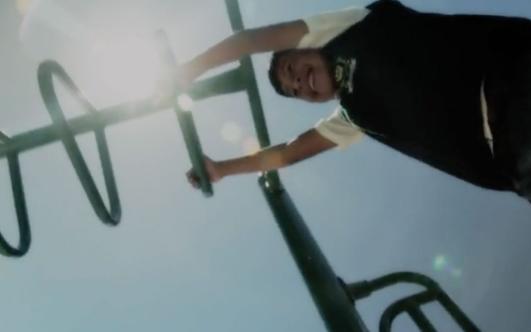 A kid enjoy some time on the monkey bars.