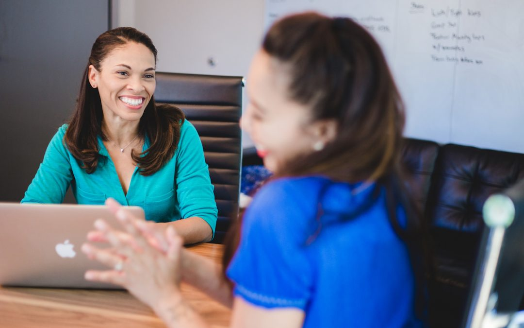 Two teachers share a laugh during a meeting.