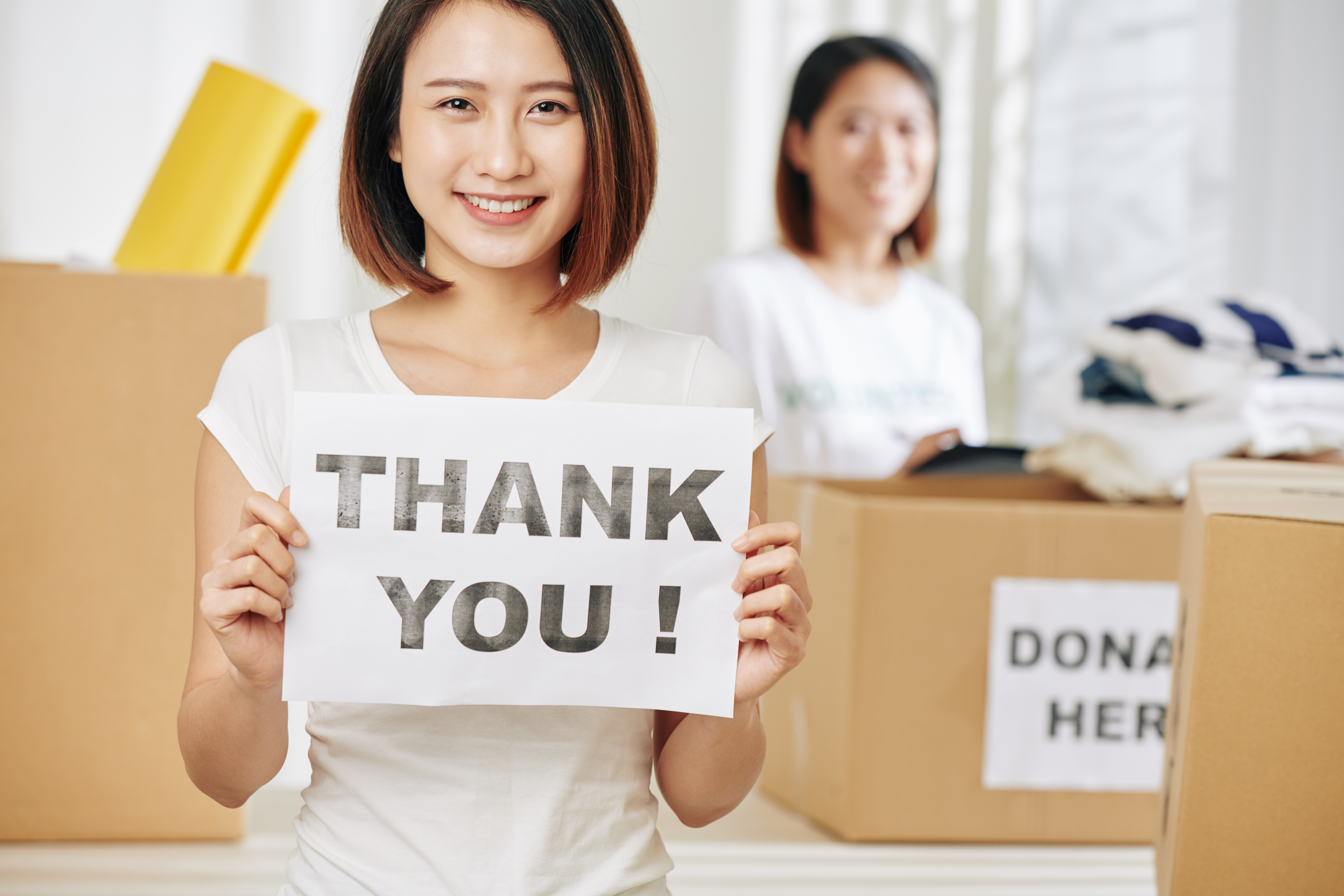 women holding thank you sign