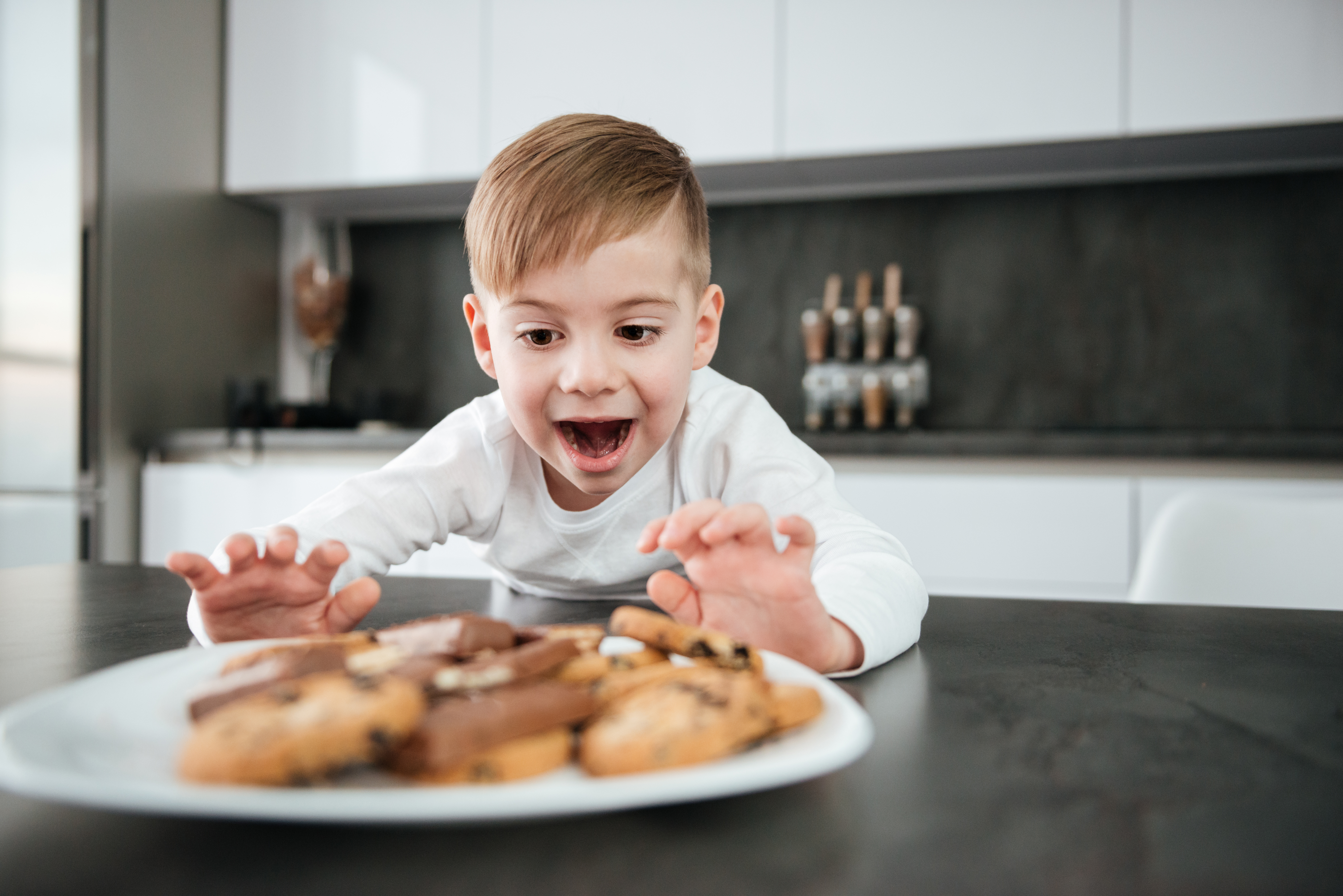 little boy excited reaching for the cookie plate