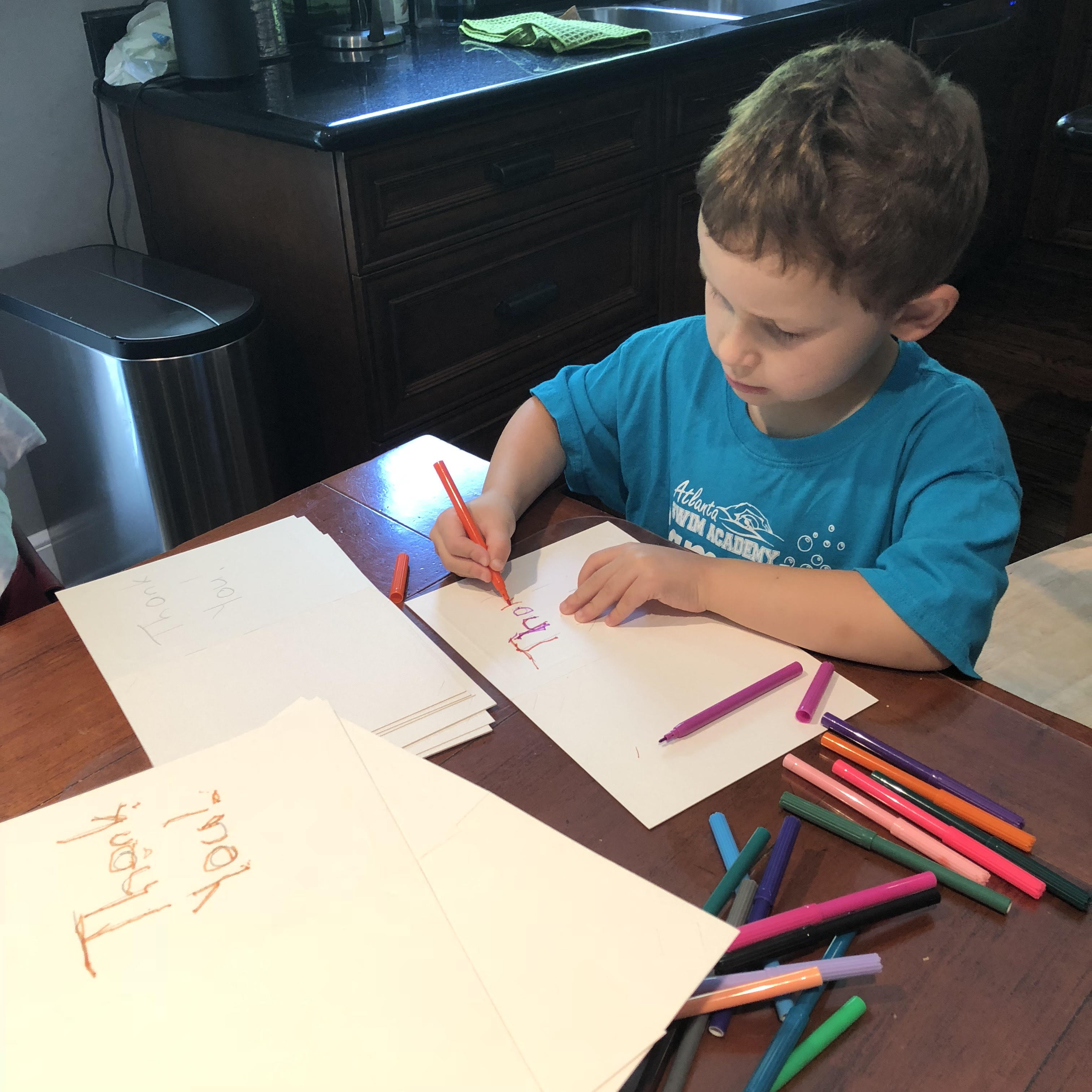 Young Student in a blue shirt writes with colored pencils